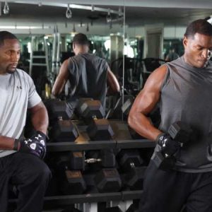 Ray Lewis is sitting on the weight bench while Monte lifts weight