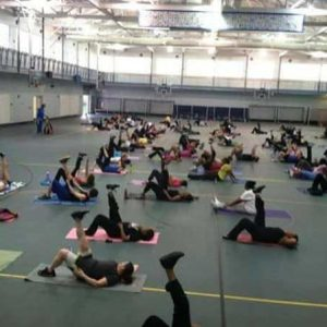 Wide shot of the gym, clients are laying down with their leg in the air