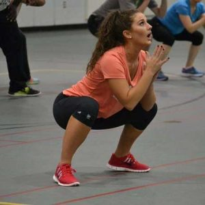 Woman in a coral shirt squatting in a gym with others doing the same.