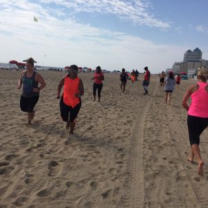 Group running on beach with Fitness trainer