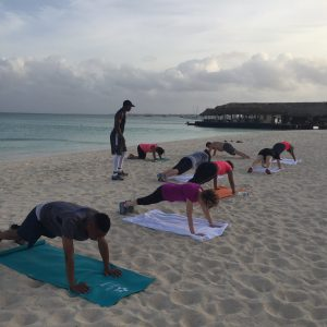 Pushups on oceanfront sands while being coached